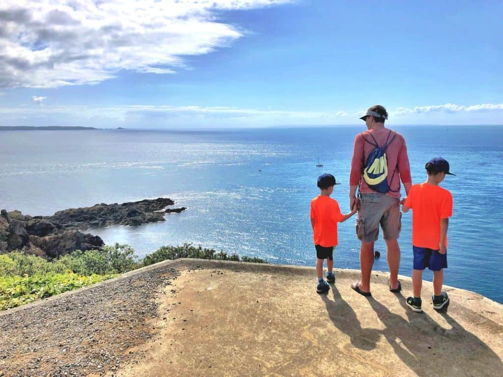 father with kids overlooking ocean