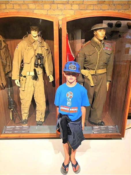 boy standing in front of wwII uniforms