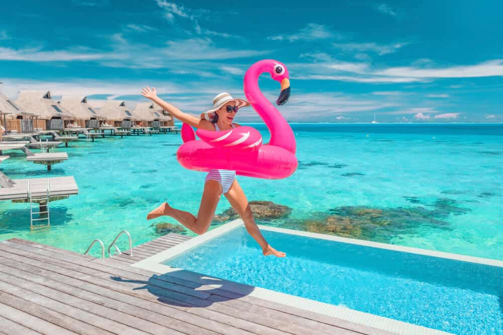 woman with pink unicorn jumping in pool