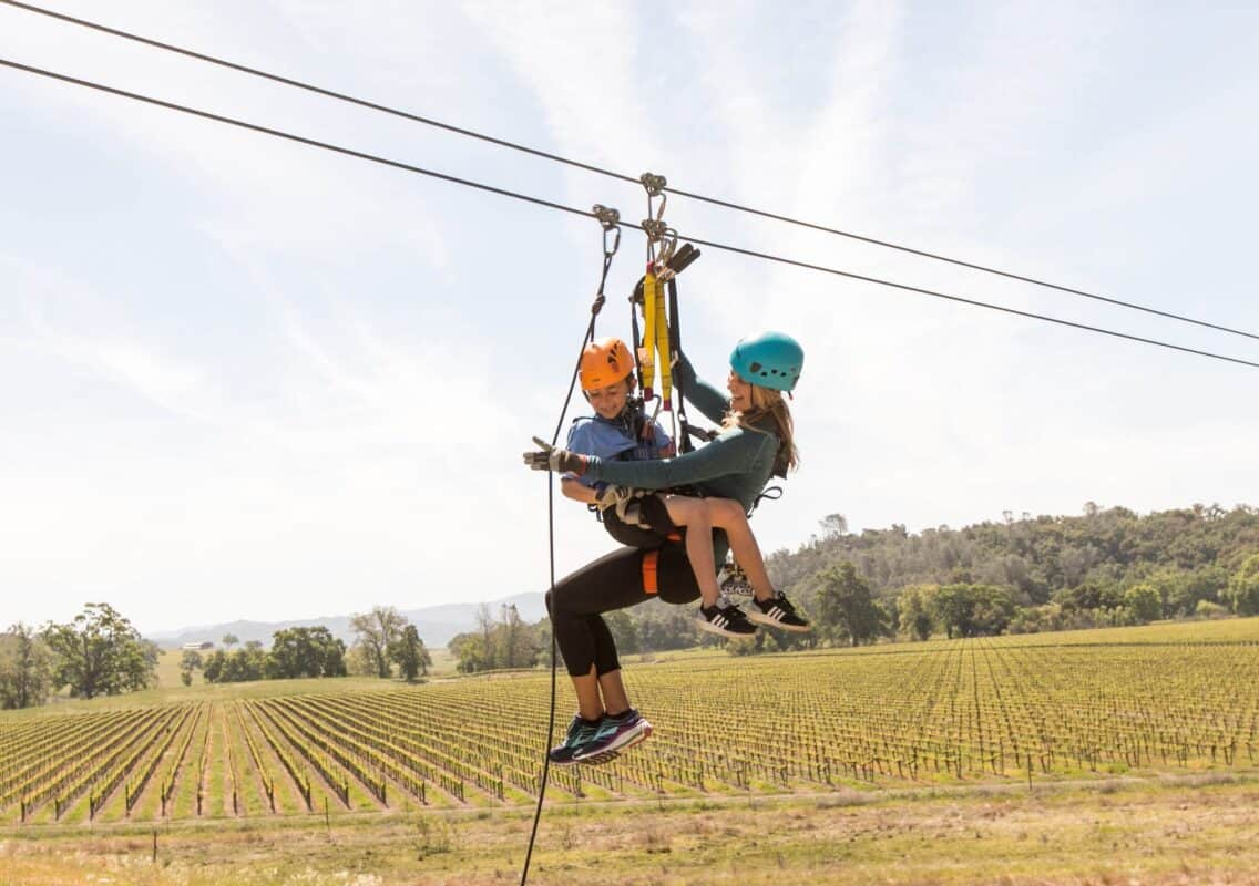 mother and child zip lining above vineyards